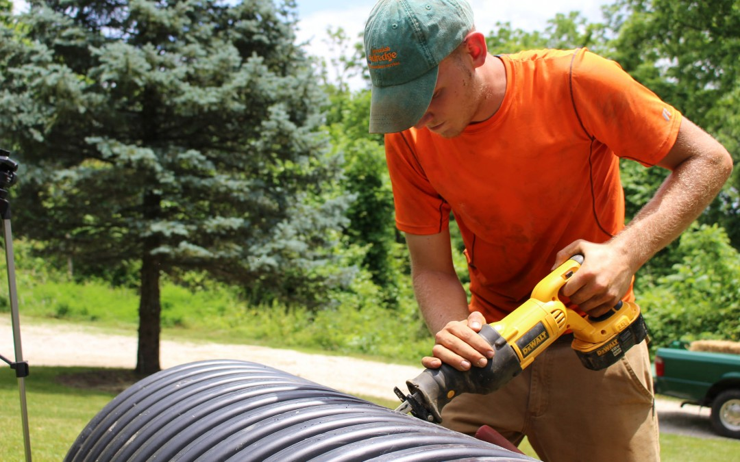Nate cutting through 24 inch corrugated pipe for a riser that will bring the main access up to grade